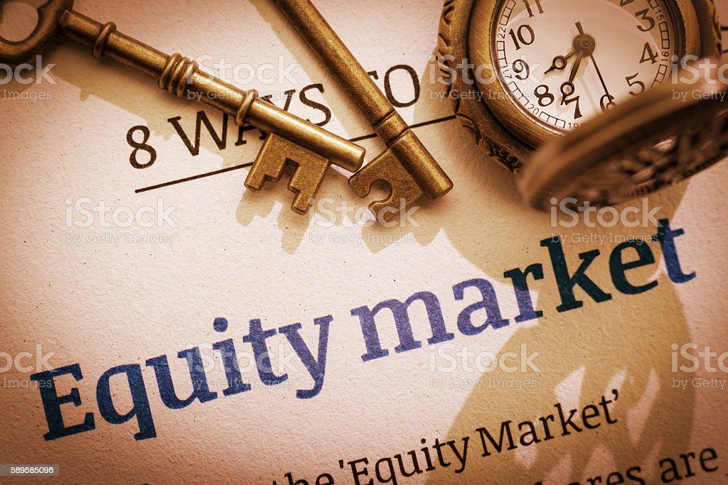Two brass keys on an equity market fundamental document. stock photo