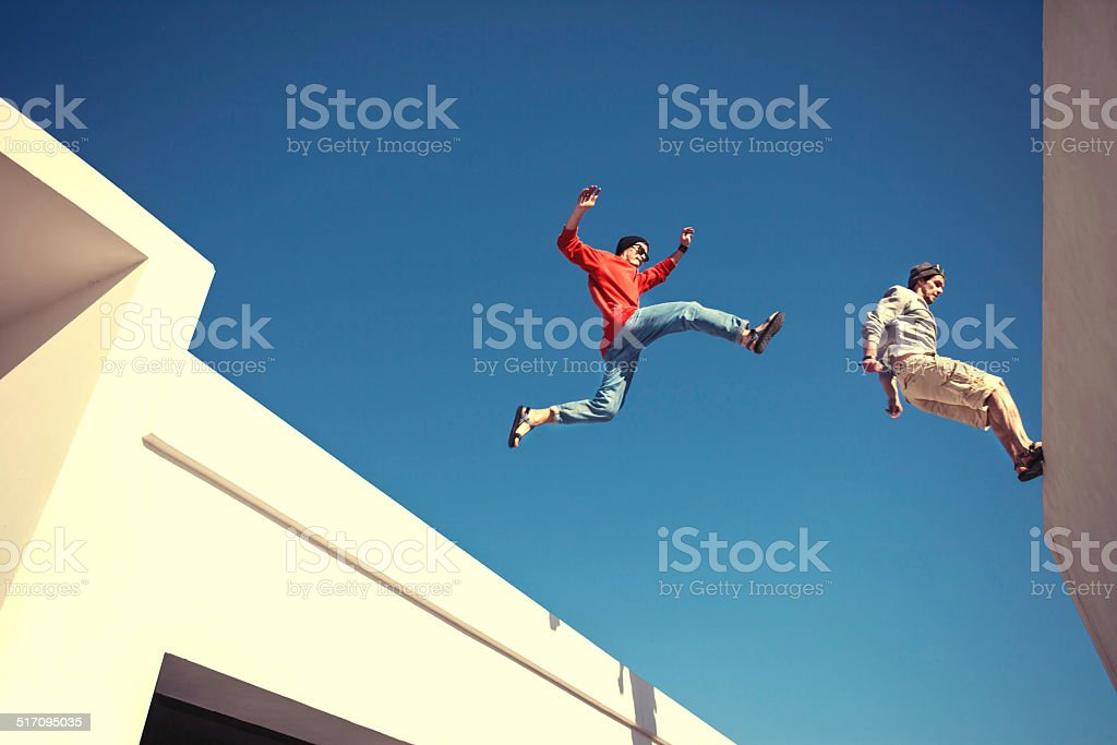 two brave men jumping over the roof stock photo