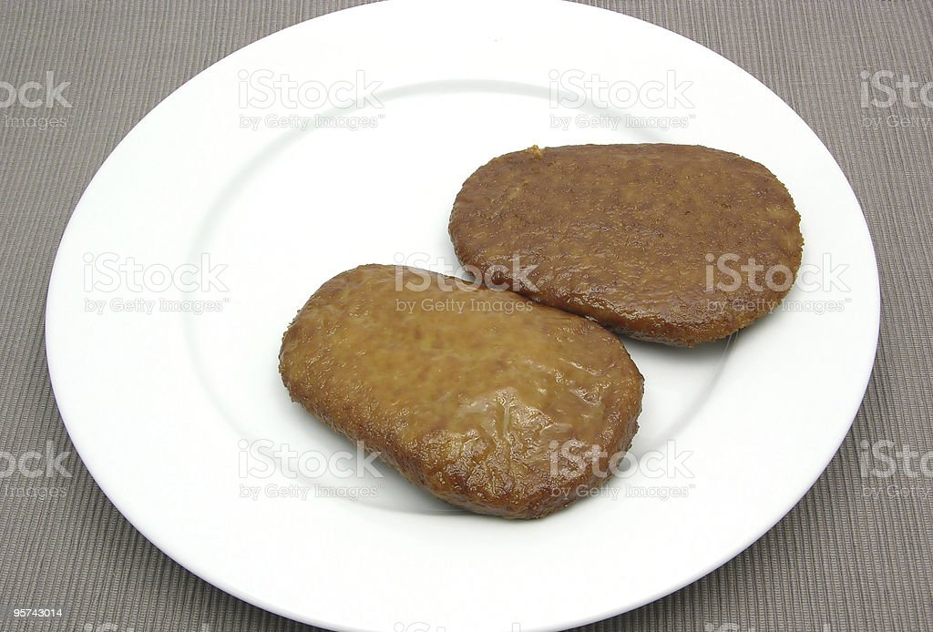Two breaded bean curd cutlets on white plate stock photo
