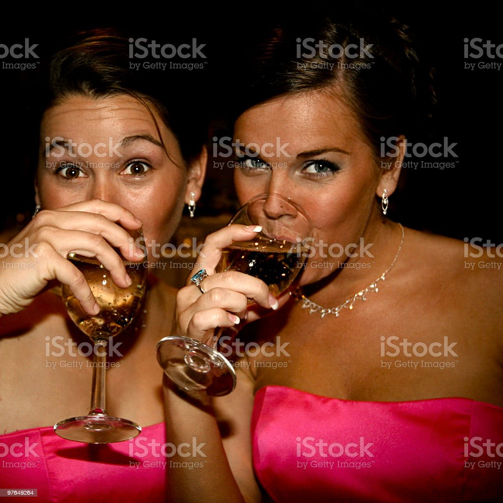 Two bridesmaids in pink dresses drinking champgane royalty-free stock photo