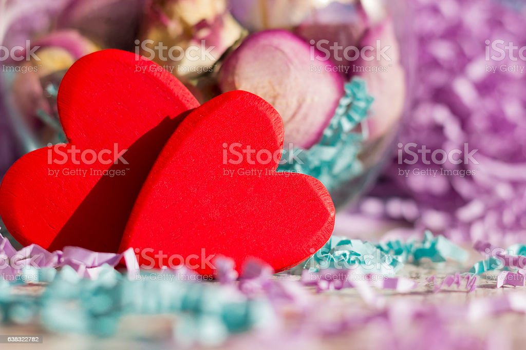 Two bright red hearts on a background of dried roses stock photo