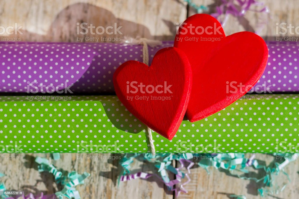 Two bright red hearts on wrapping paper. stock photo