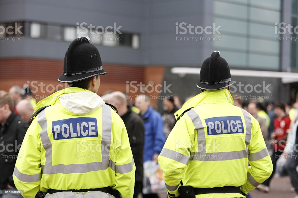 Two British Policemen-Traditional Helmets-Crowd Control. More below... stock photo