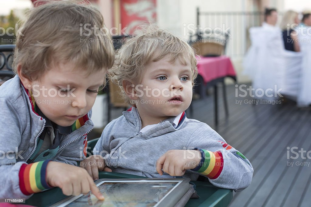 Two brother toddler boys playing with tablet pc royalty-free stock photo
