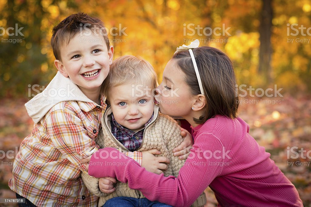 Two Brothers and Sister Hugging Outdoors on Fall Day royalty-free stock photo