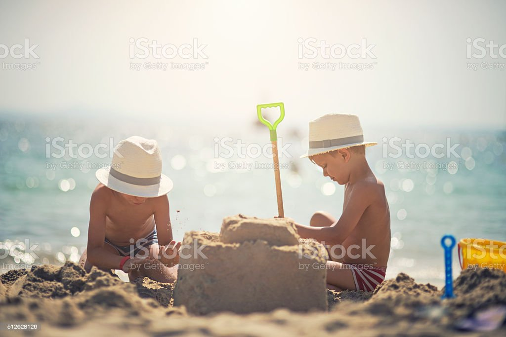 Two brothers building a sandcastle on beautiful beach stock photo