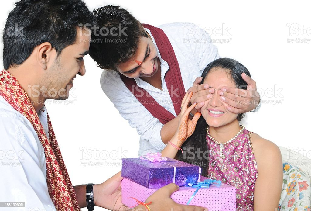 Two brothers giving surprise gift to their sister on festival. stock photo