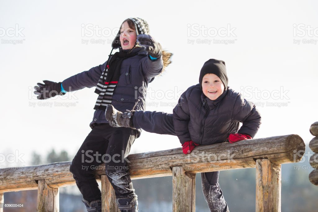 Two brothers having fun on snow stock photo