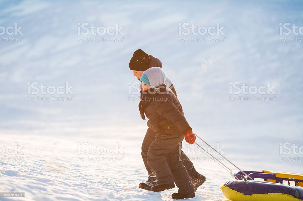 Two brothers having winter fun sliding on show stock photo