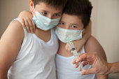 two   brothers in medical mask looking at hand with syringe