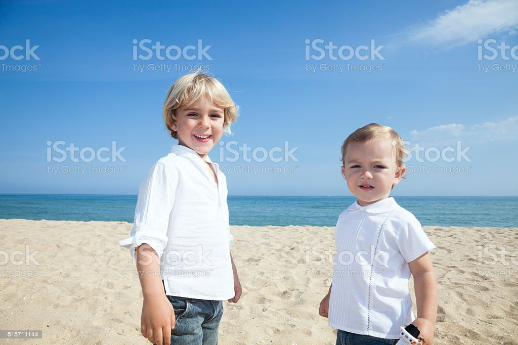 Two brothers in the beach stock photo