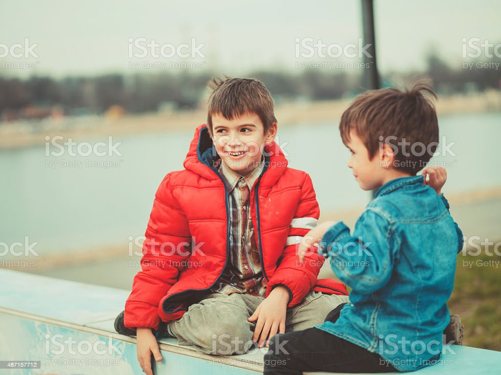 two brothers playing outdoors stock photo