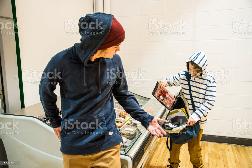 Two brothers shoplifting bacon stock photo