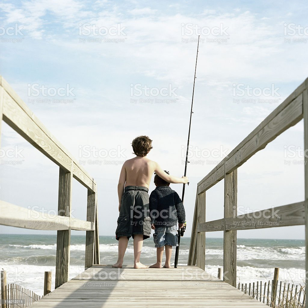 Two brothers with a fishing rod at the beach royalty-free stock photo