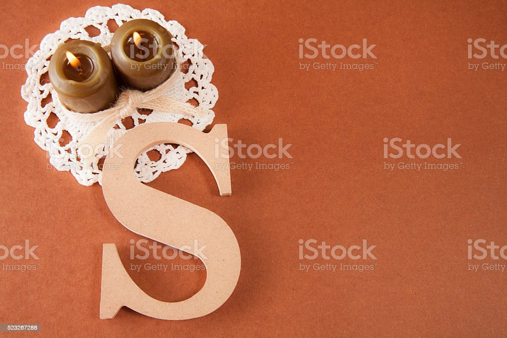 Two brown burning candles with initial 'S' and copyspace. stock photo