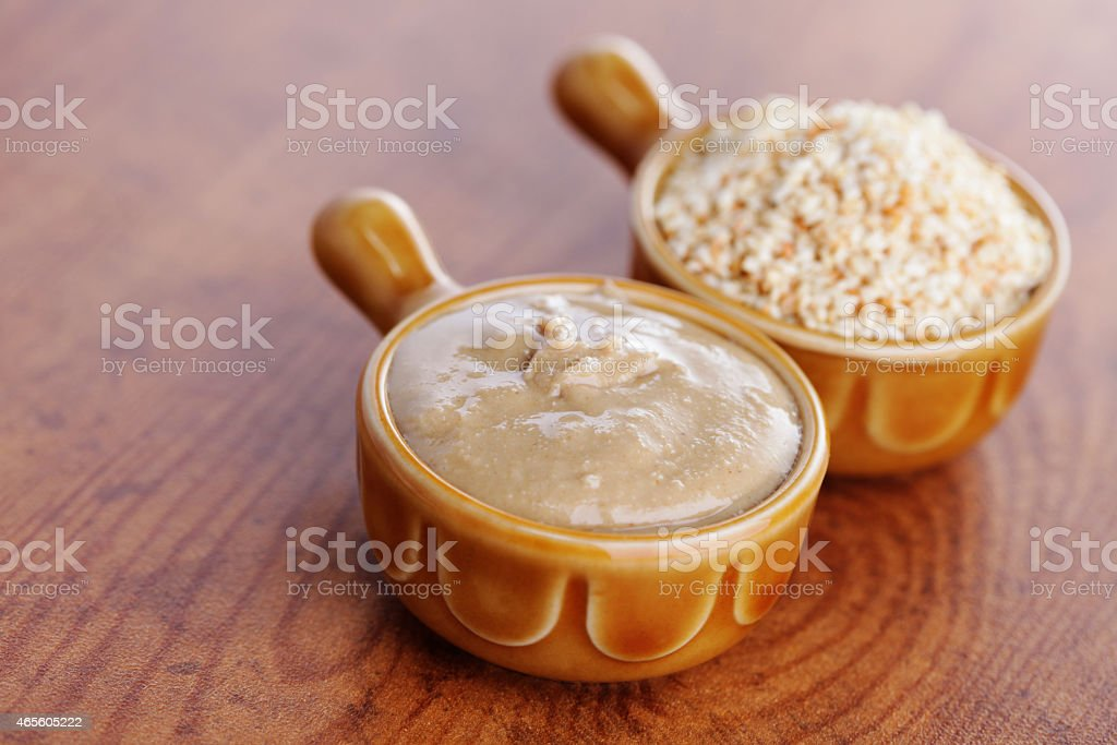 Two brown mini crocks of tahini on a wooden table stock photo