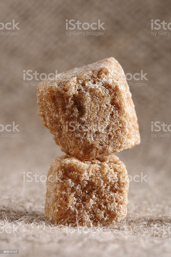 two brown sugar cubes on hessian background royalty-free stock photo