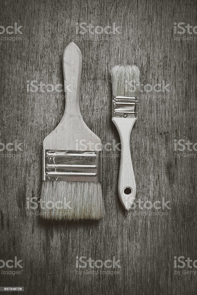 two brushes to paint on a wooden table. stock photo