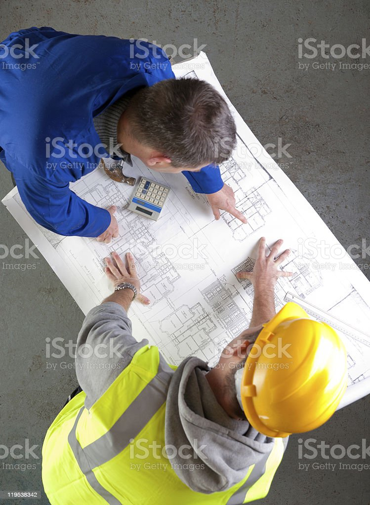 Two builders discuss construction blueprints royalty-free stock photo