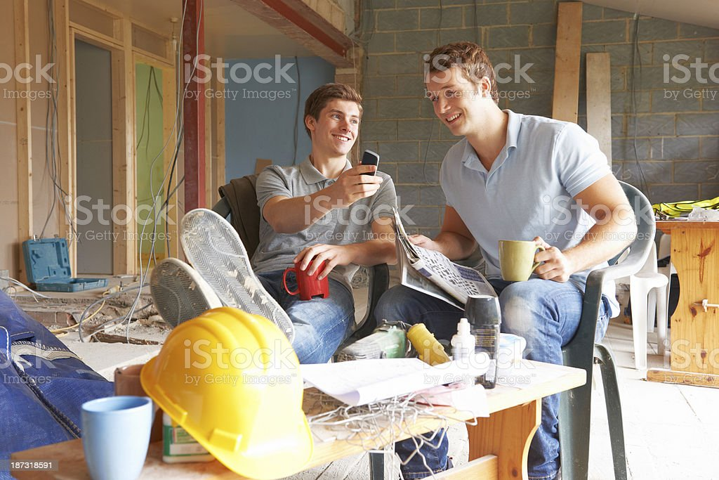 Two builders smiling at a phone during a break on site royalty-free stock photo