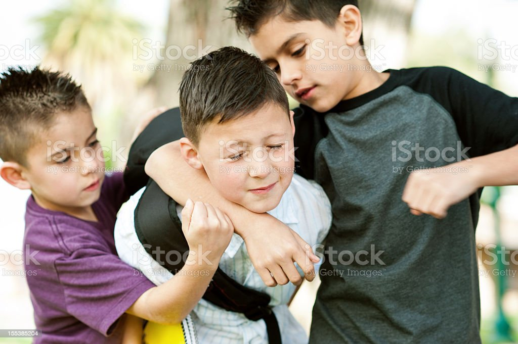 two bullies put kid in headlock stock photo