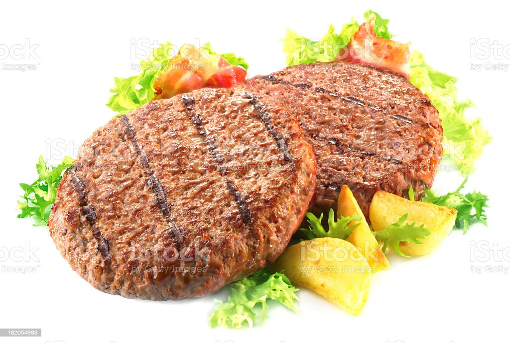 Two burger patties atop bacon and lettuce stock photo