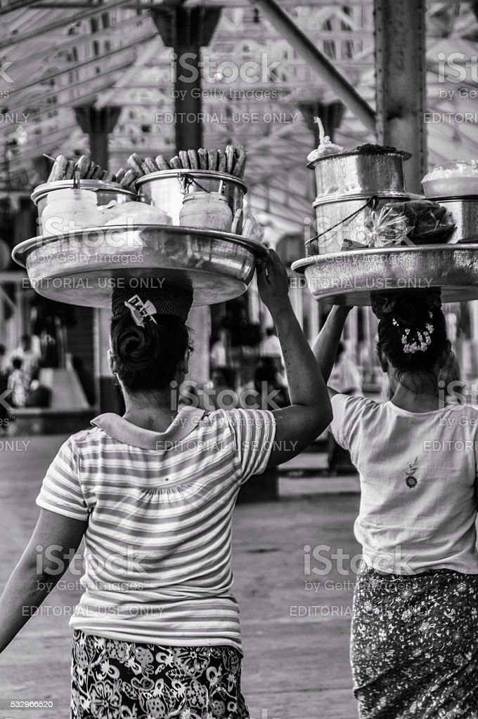 Two Burmese women are carrying food on their head. stock photo