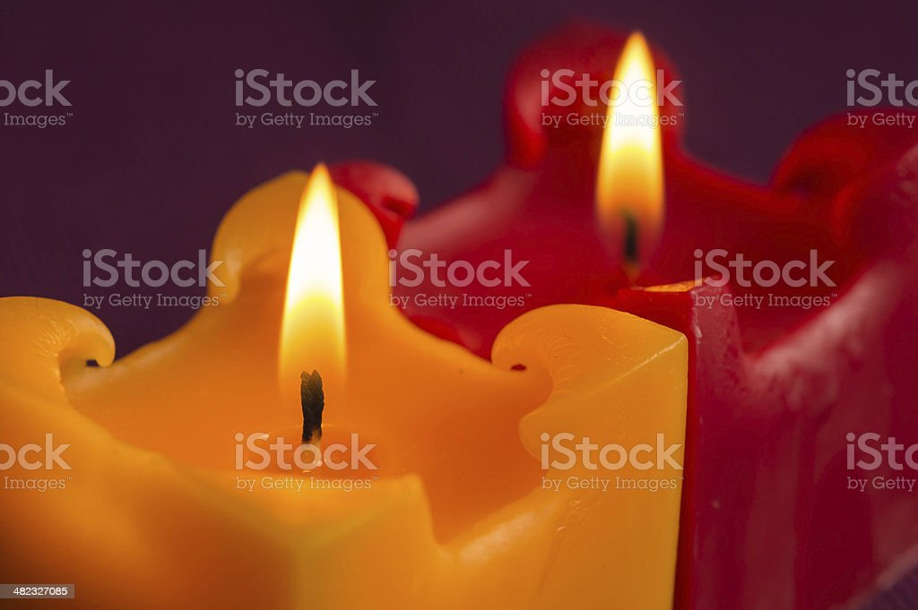 Two burning candles of red and yellow color close up stock photo