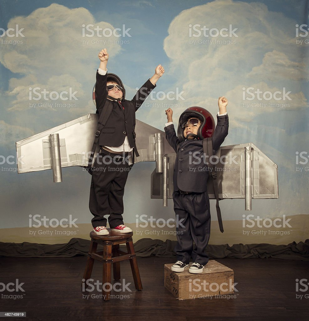 Two Business Boys wearing Jetpacks Fly High stock photo
