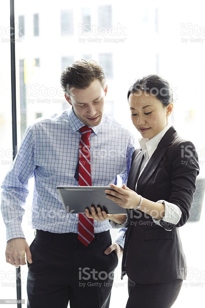 Two business colleagues looking at a tablet outdoors stock photo