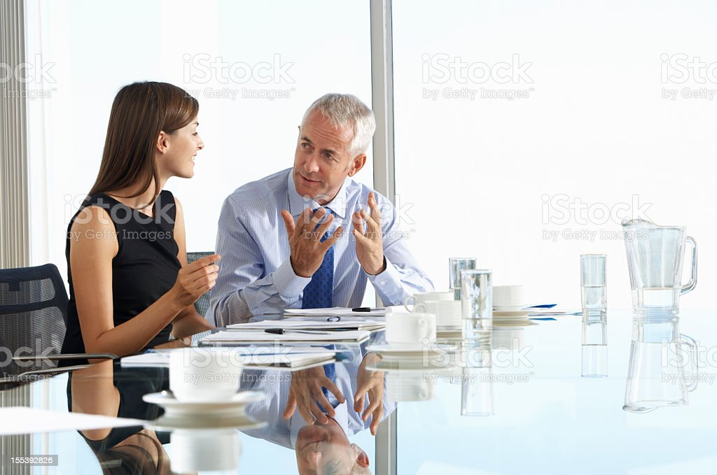 Two Business Colleagues Sitting Around Boardroom Table stock photo