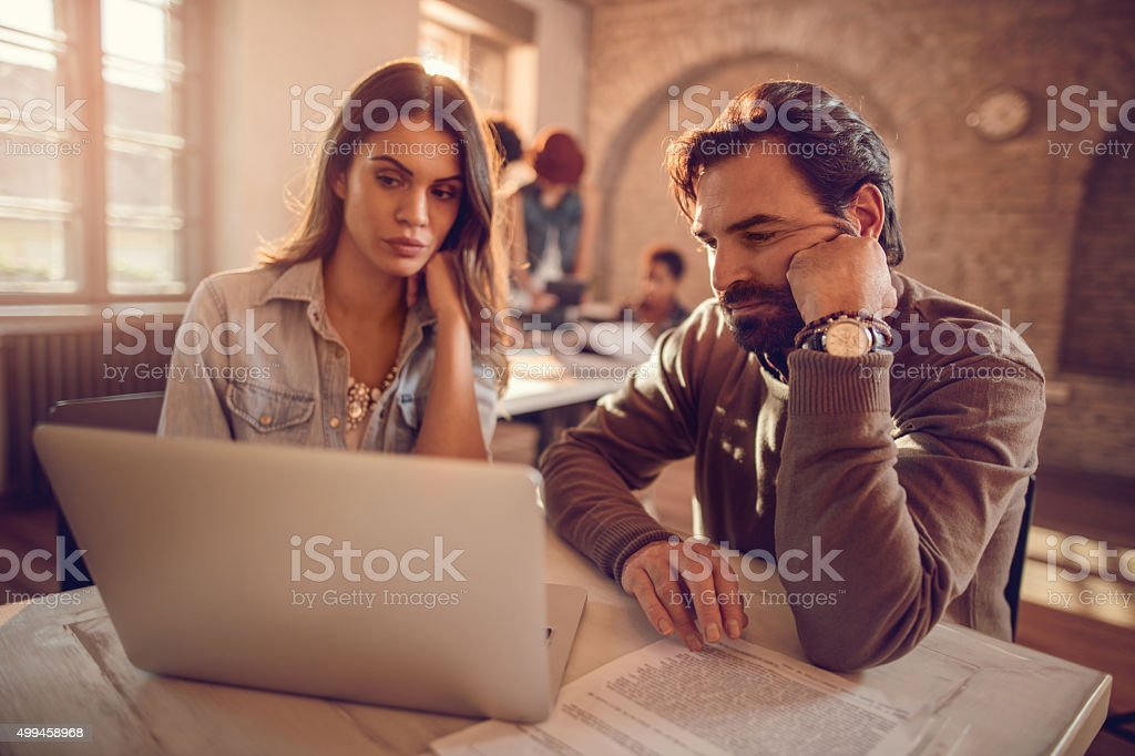 Two business colleagues working together on a laptop at office. stock photo