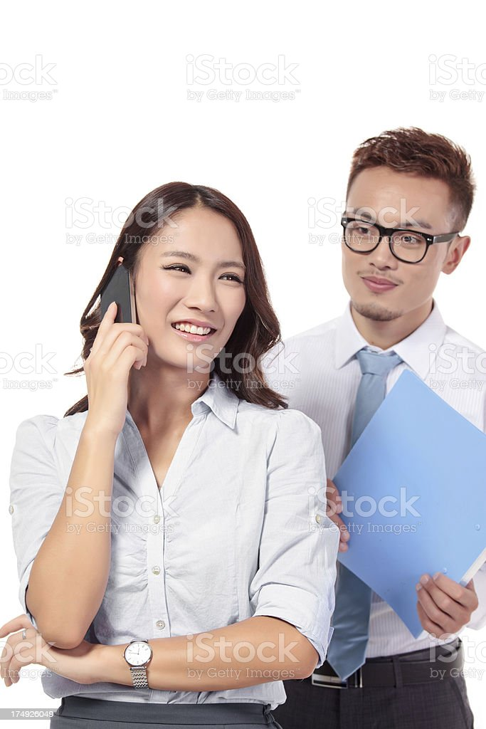Two business coworkers standing together and looking at a smartp royalty-free stock photo