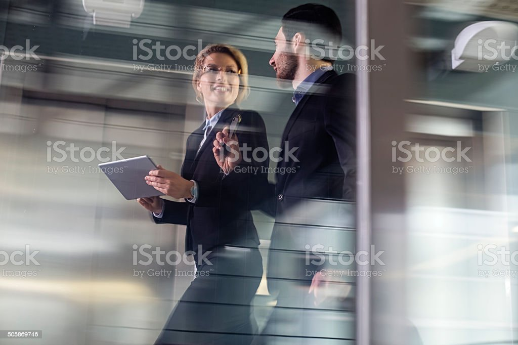 Two Business coworkers walking along elevated walkway stock photo