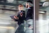 Two Business coworkers walking along elevated walkway