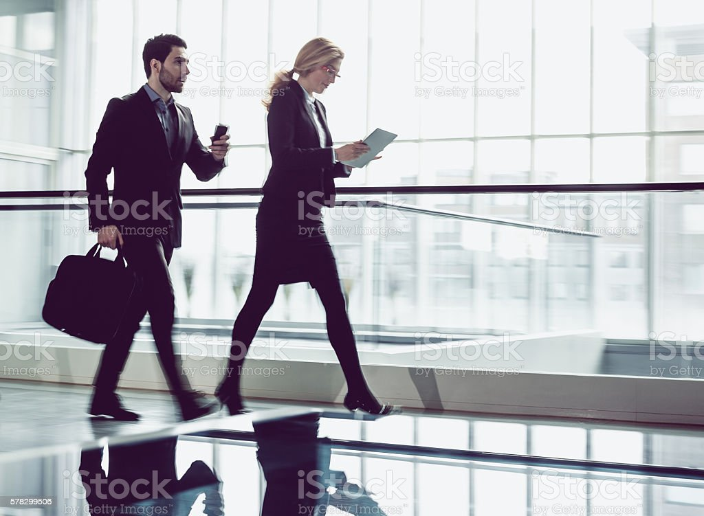 Two Business coworkers walking along office coridor stock photo