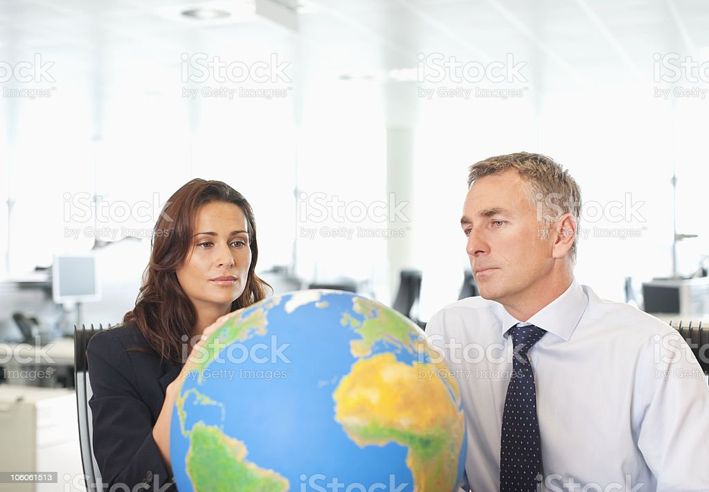Two business executives looking at a globe royalty-free stock photo
