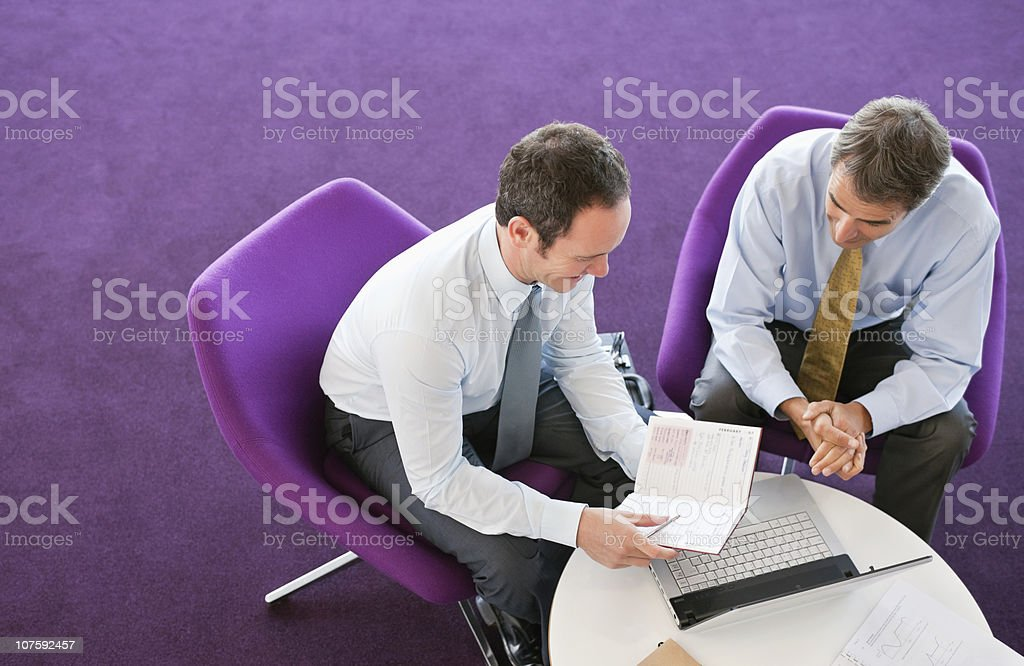 Two business executives sitting with laptop discussing on report in office cafeteria royalty-free stock photo