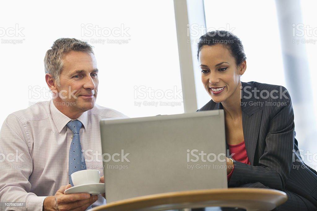 Two business executives working on laptop at office cafeteria royalty-free stock photo