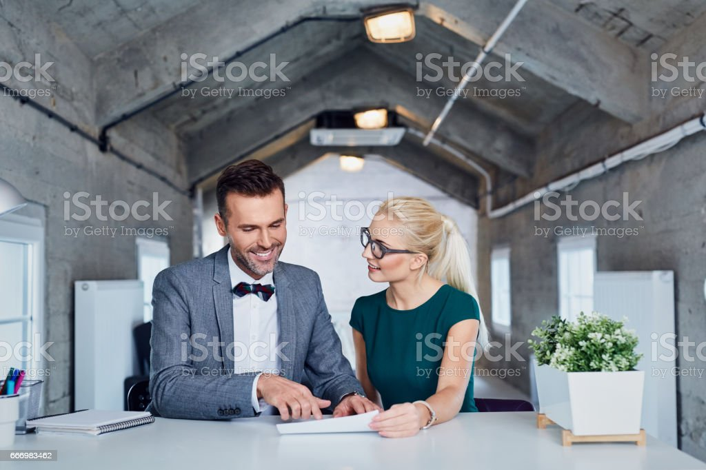 Two business managers analyze contract in modern office. stock photo