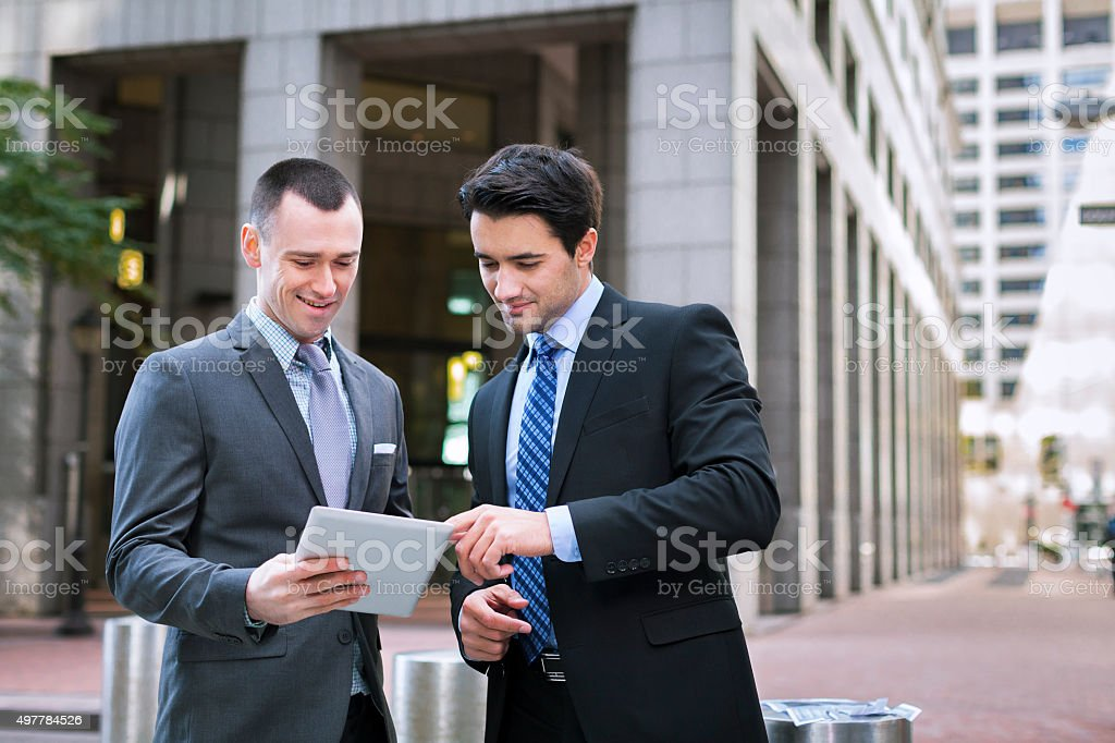 Two business men looking at news on tablet stock photo
