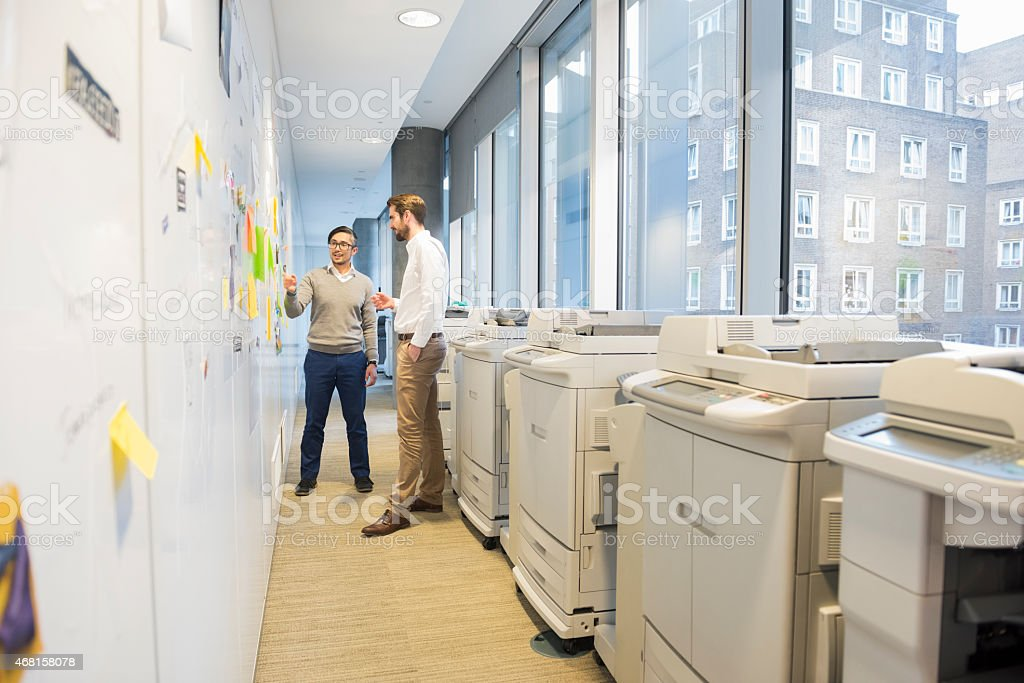 Two business men talking by notes on a wall and  printers. stock photo