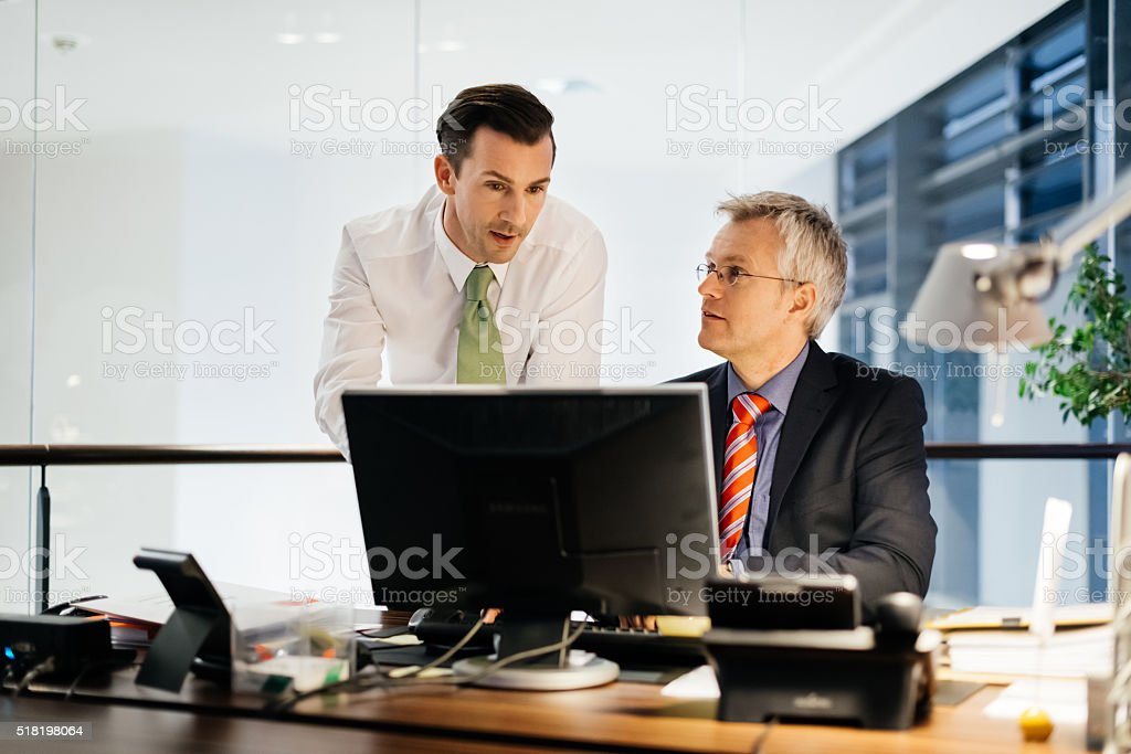 Two Business Men Working Late in illuminated office stock photo