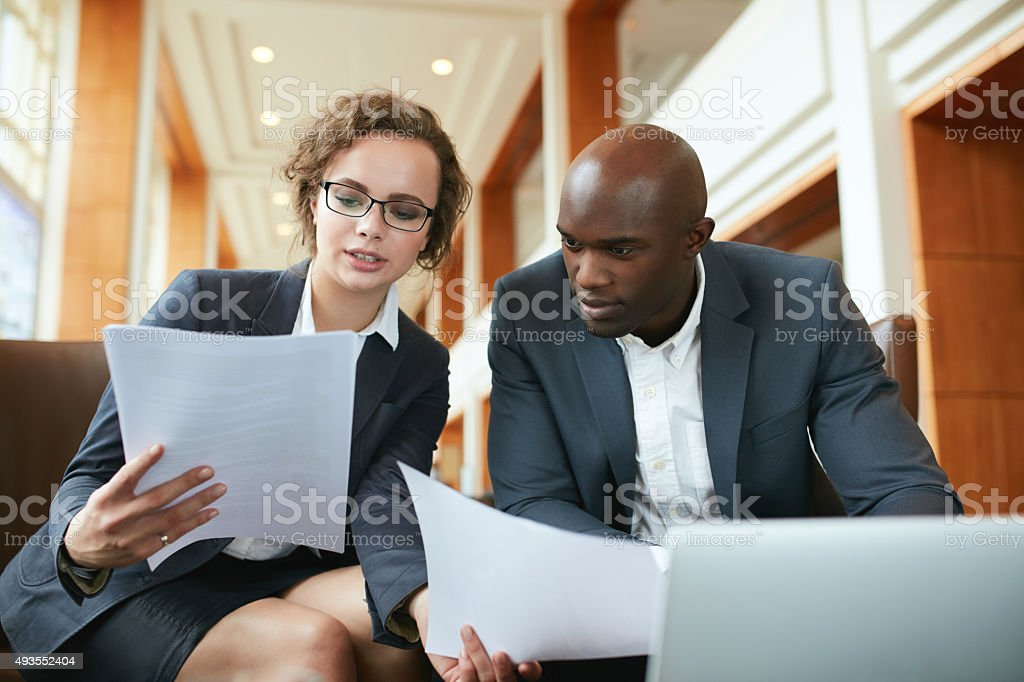Two business partners sitting in cafe and discussing contract. stock photo
