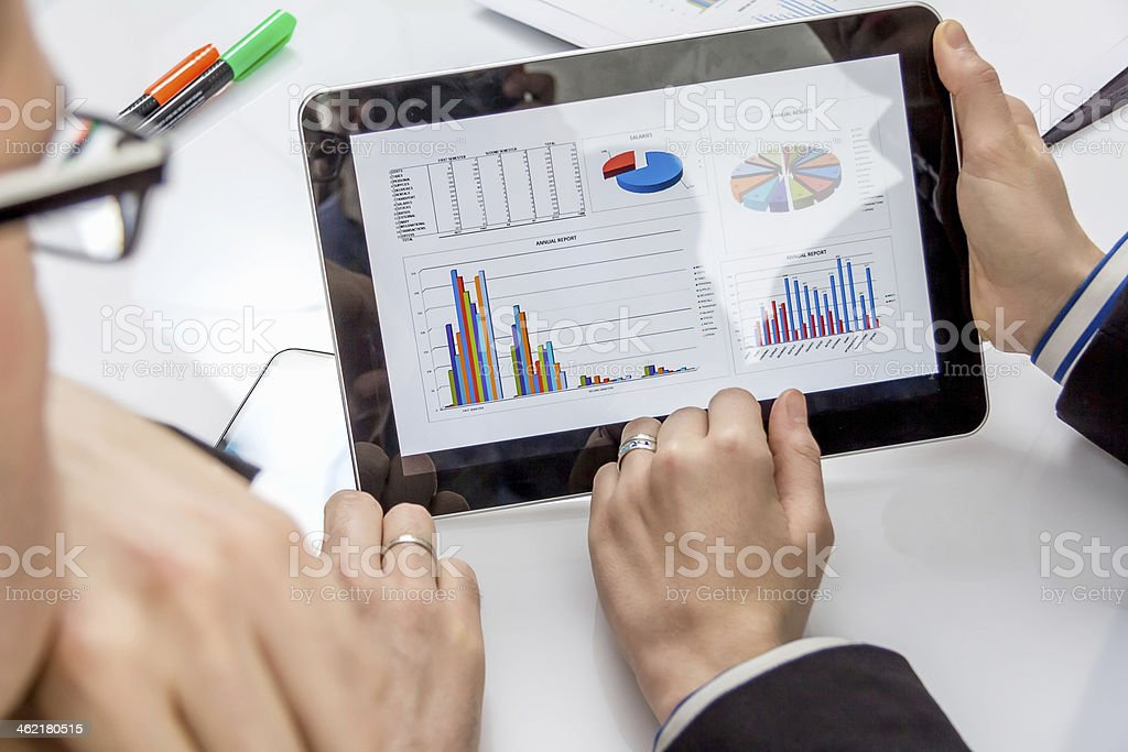 Two business people analyzing documents on a tablet royalty-free stock photo