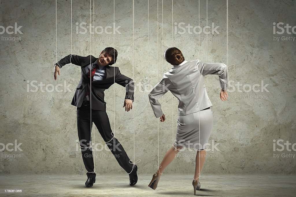 Two business people being controlled by a puppeteer stock photo