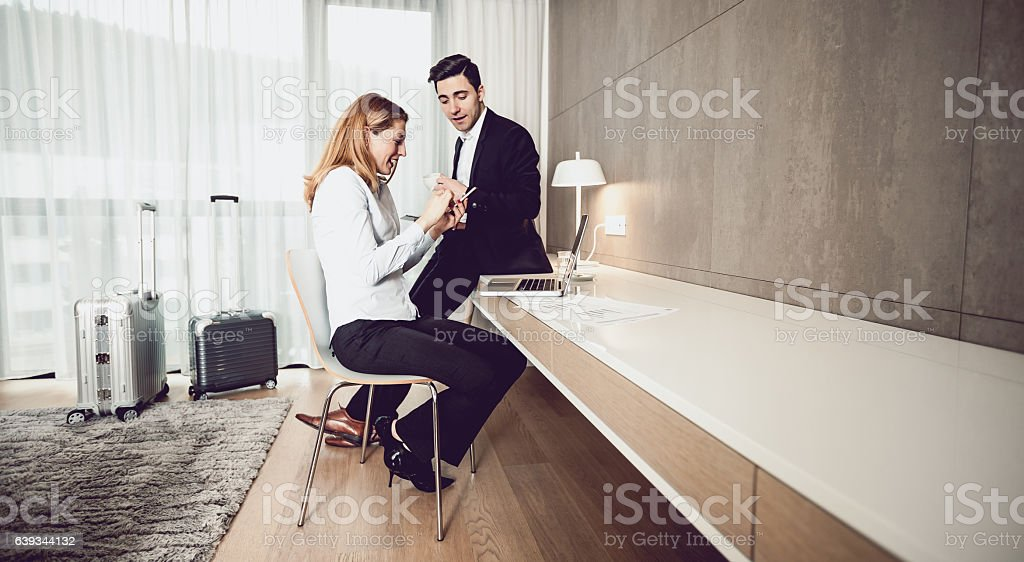 Two Business People Discussing in a Hotel Room, Using Laptop stock photo