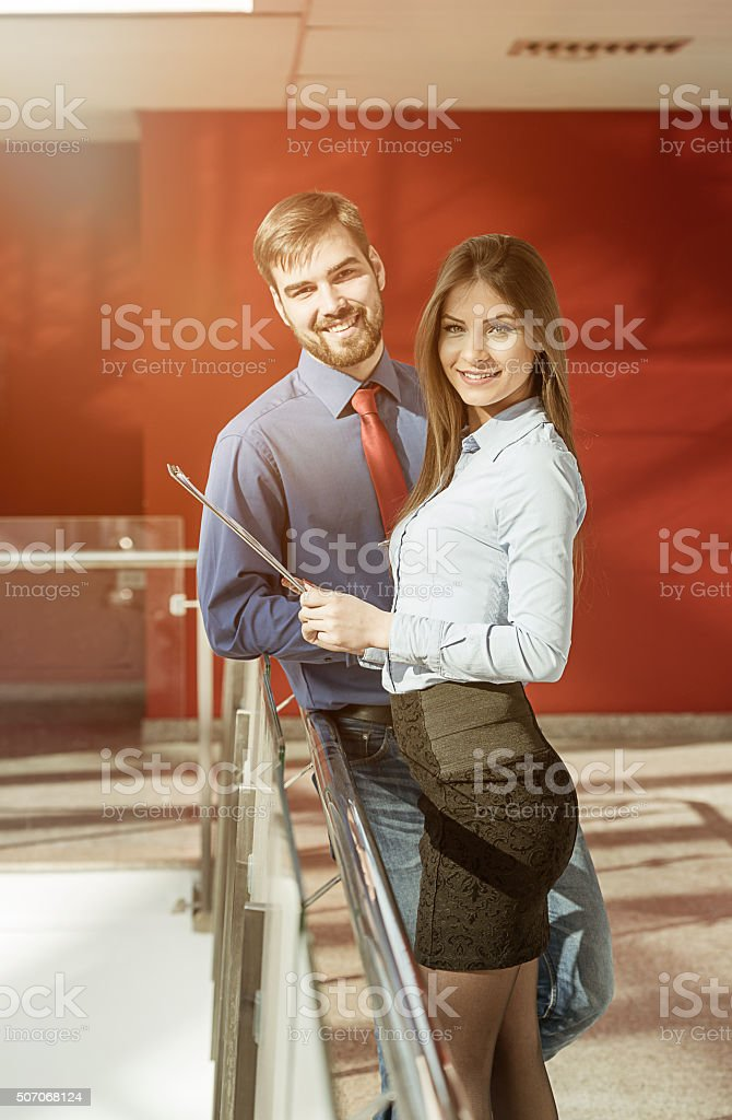 Two business people in modern office building discussing project proposals stock photo