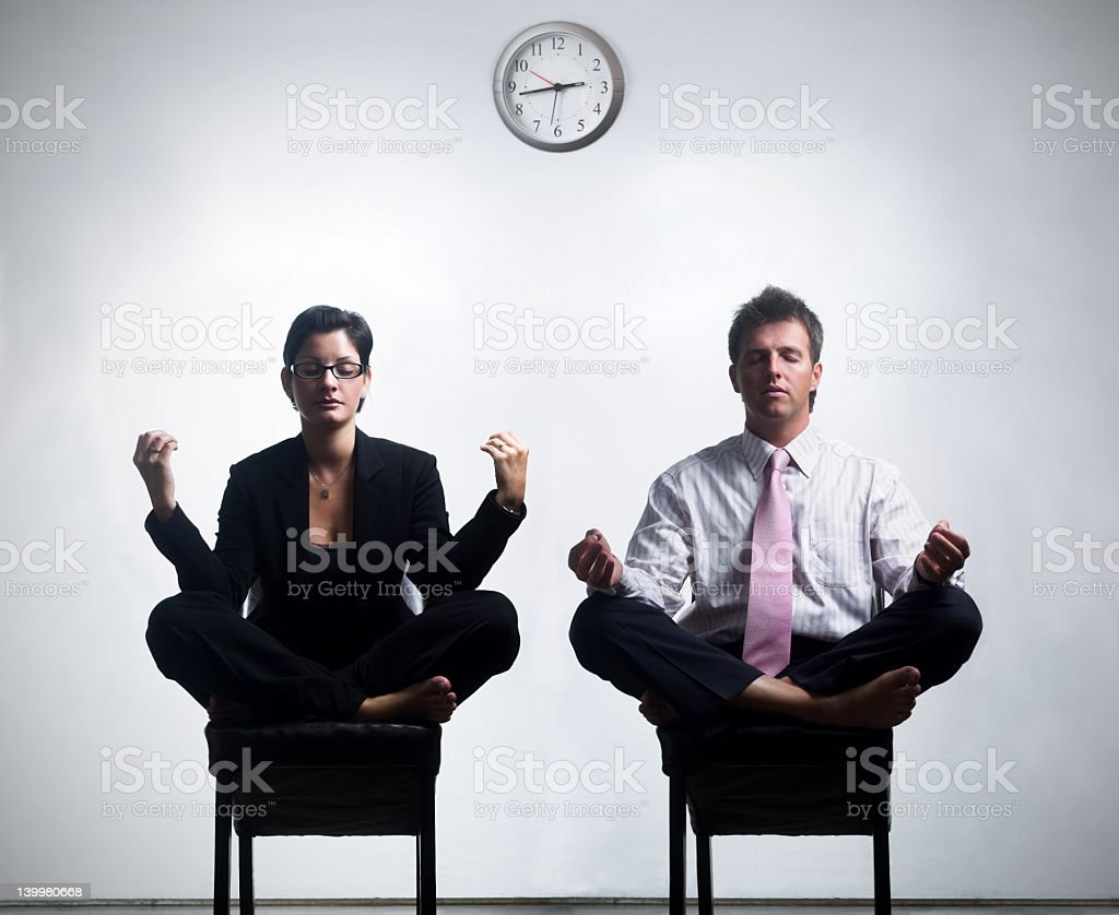 Two business people meditating during their break  stock photo