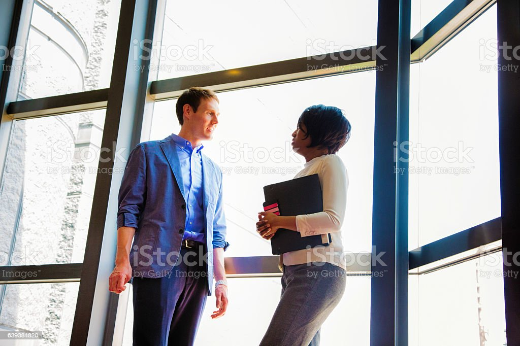 Two business people meet during a break at the office stock photo